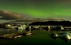 the floating icebergs of jokulsarlon under the northern lights
